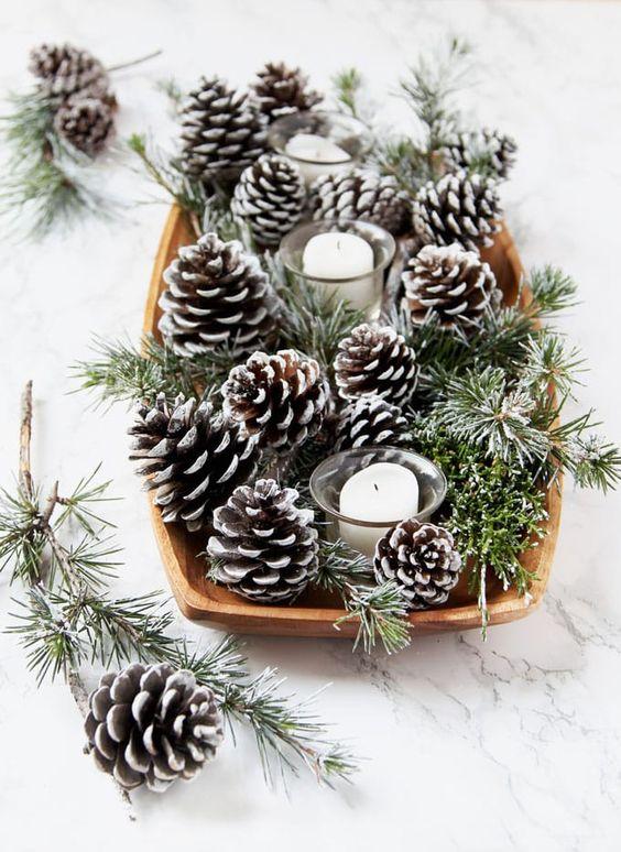 Centro de navidad con piñas cubiertas de nieve