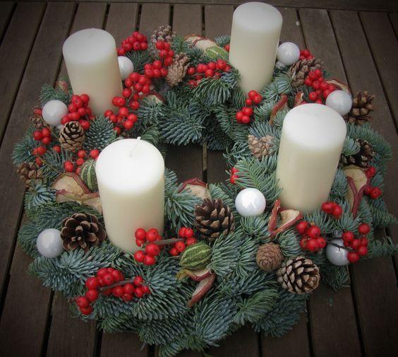 Corona de adviento con velas blancas y flores rojas Navidad