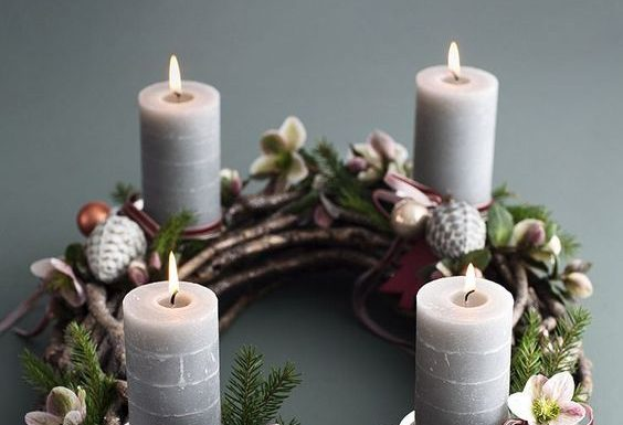 Corona de adviento con velas blancas y piñas